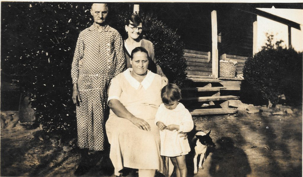 Photo of four family members sitting in their farmhouse yard in 1933