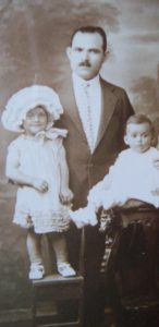 A father stands in a suit behind his two small children for a photo.