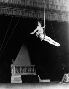 vintage black and white photo of Barbette sitting on a trapeze