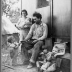 Black and white image of a migrant farmer surrounded by his family.