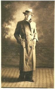 sepia tone photograph of a handsome young man in a trenchcoat and wearing a fedora
