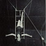 black and white photo of a circus performer handing upside down from a swinging ladder