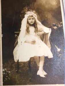 A girl in First Communion dress holding a cup and rosary