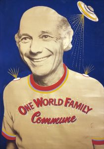 Picture of a man wearing One World Family Commune t-shirt with a flying saucer over his head.