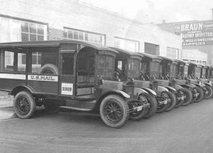 A line of 1930s postal trucks in a parking lot
