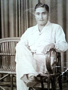 Younger Filipino gentleman sitting in a chair with his legs crossed.